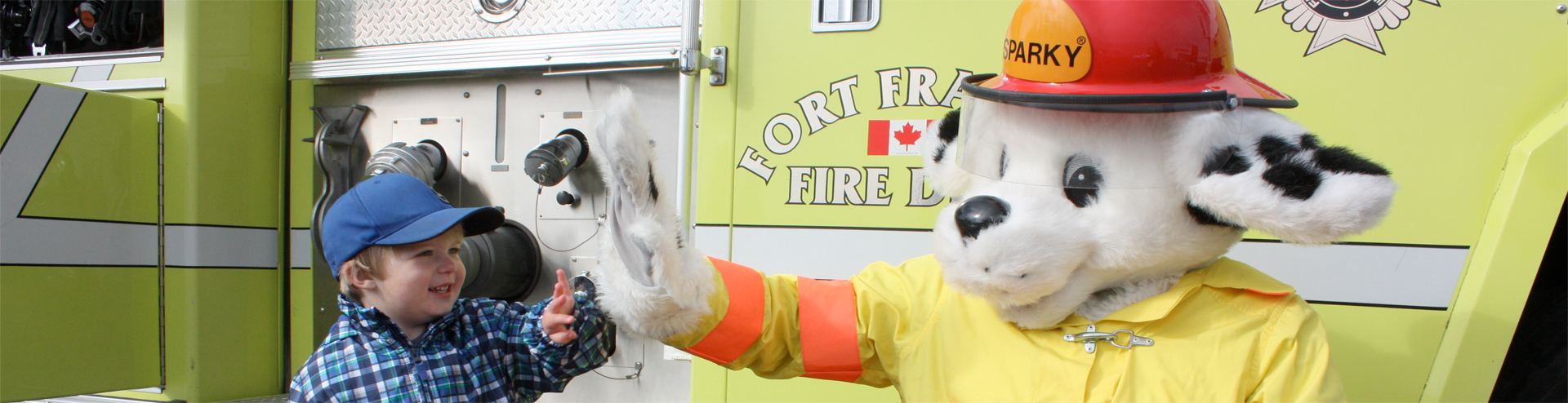 Little kids meeting Sparky the dalmation, next to the Town of Fort Frances fire truck